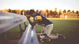 American Football speler knielt en bidt bij een bankje.