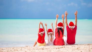 Familj i tomteluvor firar jul på stranden
