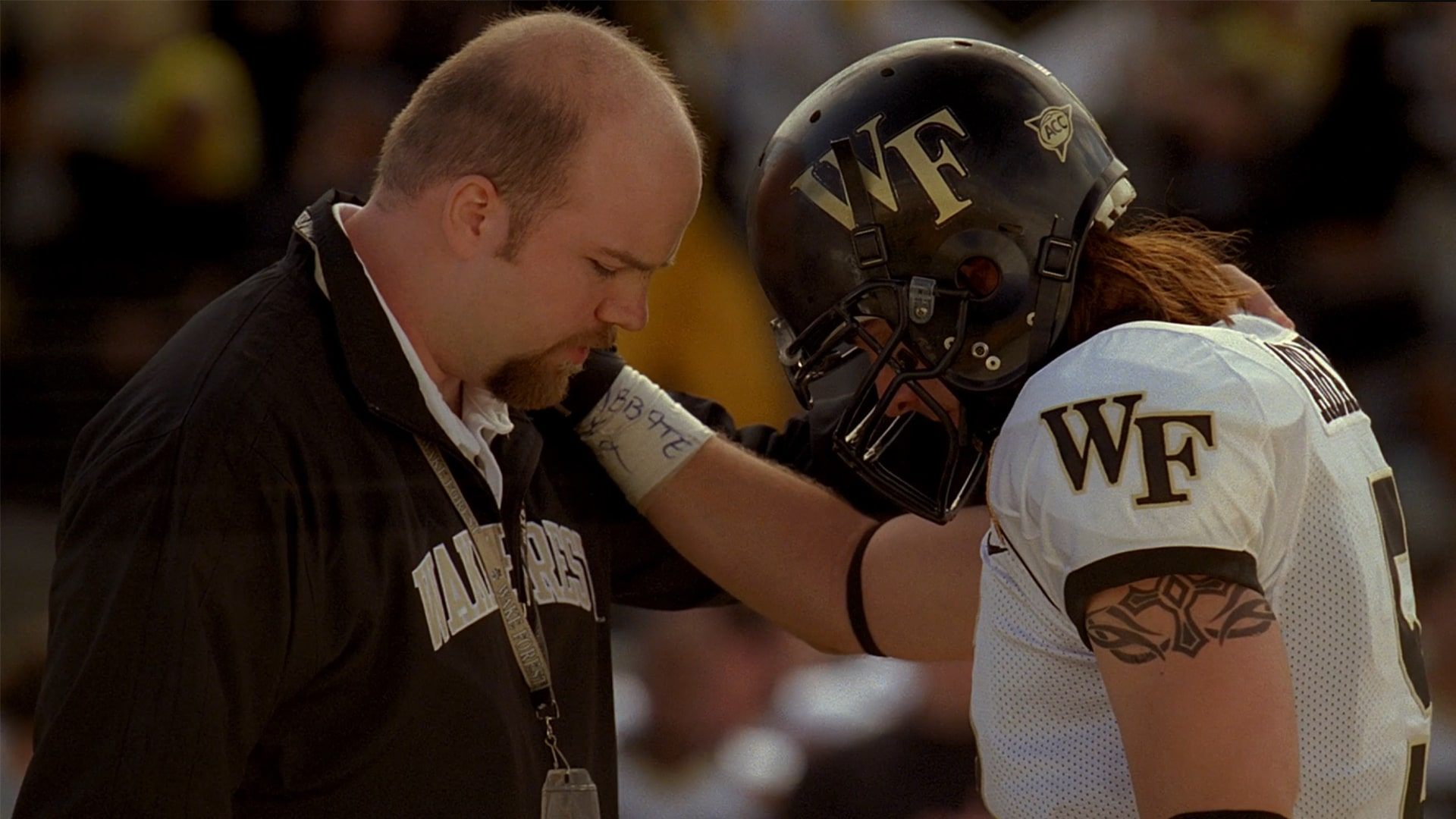 Still uit 'The 5th Quarter'. Coach en American Football spelen bidden voor de wedstrijd.